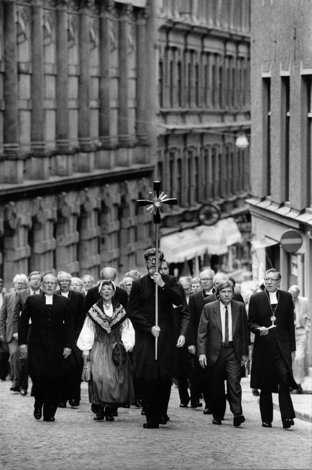 Civilminister Bo Holmberg, tillsammans med ärkebiskop Bertil Werkström till höger, går i täten för kyrkomötets procession från riksdagshuset till Storkyrkan i Stockholm augusti 1986. Prästen Per Harling bär korset.