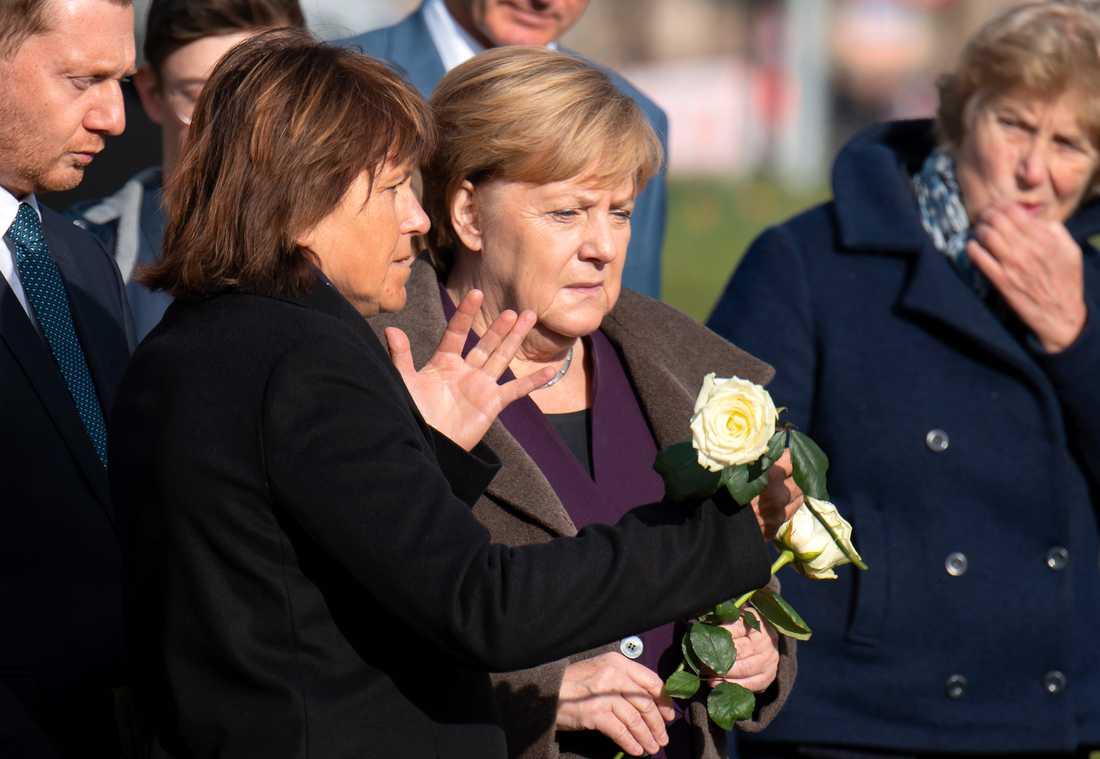 Angela Merkel (mitten) lade ned blommor på minnesplatsen i Zwickau för att hedra offren. På bilden syns också Zwickaus borgmästare Findeiss (vänster om Merkel) och Sachsens regionala regeringschef Michael Kretschmer i vänstra hörnet.
