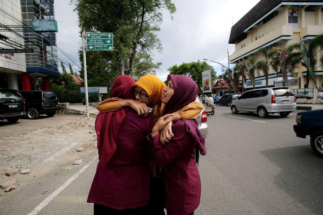 Två kvinnor kramar om varandra och ber efter jordbävningen i Banda Aceh.