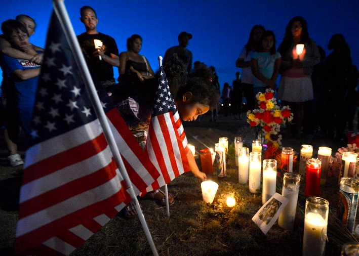 Myia Young, 4, tänder ett ljus för offren som sköts ihjäl under premiären av nya Batmanfilmen den 20 juli.