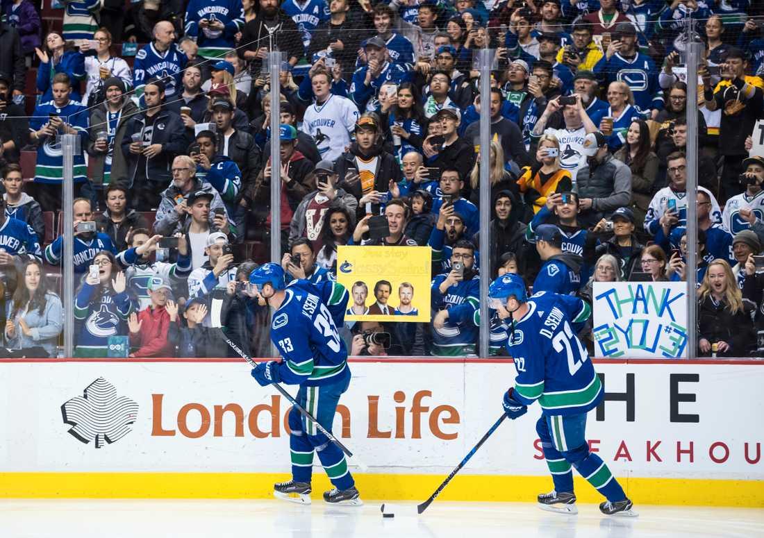 Vancouvers Henrik Sedin, vänster och Daniel Sedin hyllas ute på isen inför sin sista hemmamatch för Vancouver mot Arizona i natt svensk tid.