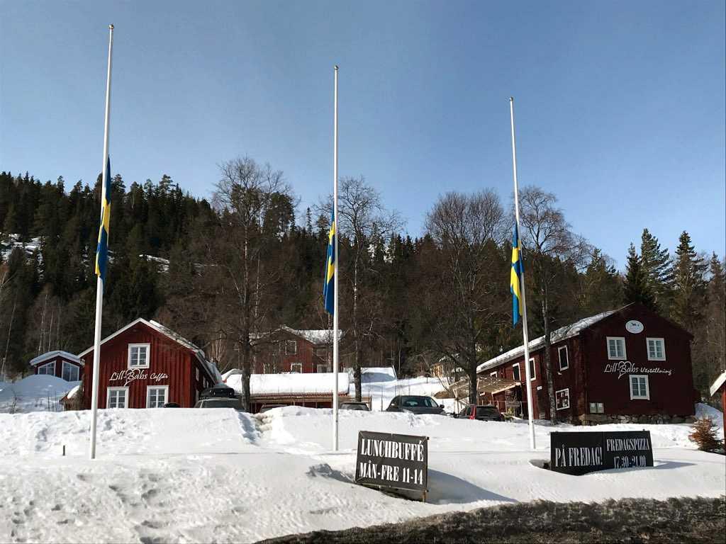 """Flaggor på halv stång utanför Lill-Babs """"caffär"""" i Järvsö."""