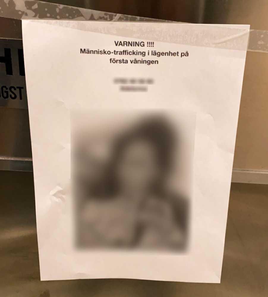 """En lapp i trappuppgången har texten """"Varning!!!! Människo-trafficking i lägenhet på första våningen"""" följt av ett namn, telefonnummer och en bild. Numret är kopplat till en sida med eskort-tjejer."""