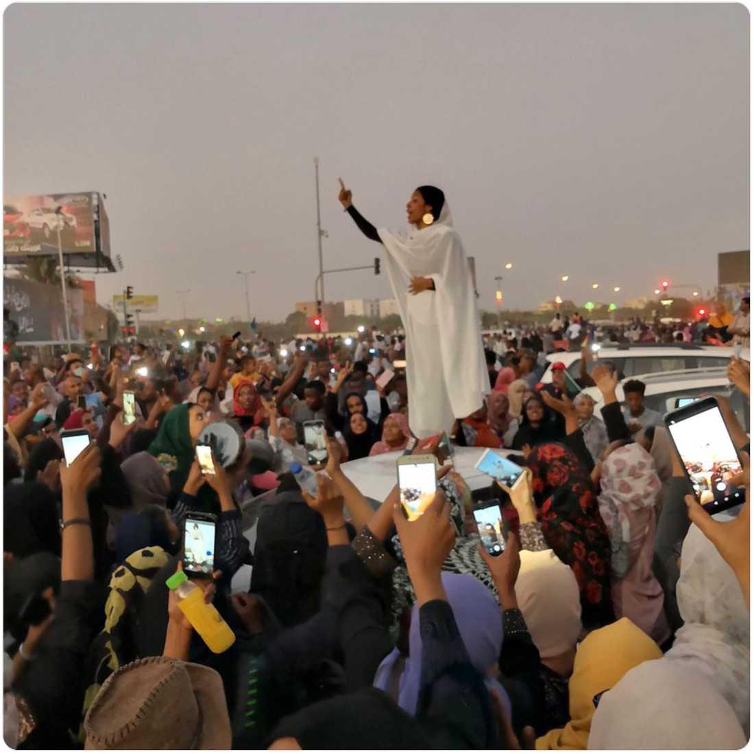 Den unga sudanesiska kvinnan Alaa Salah, 22, står på en bilmotorhuv i huvudstaden Khartoum. Hon har höjt ena armen och har ett finger i luften, och leder protestsången med hjälp av alla de människor som samlats kring henne.
