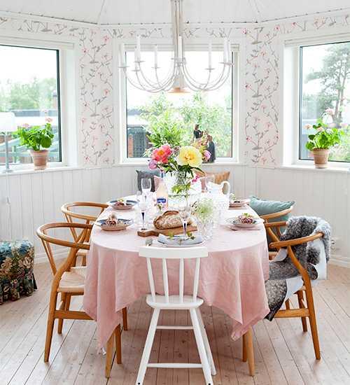 Från hemmets matrum har man en härlig utsikt. Matbord från Svenska hem och Y-stolar från Hans J. Wegner. Vit barnstol från Ikea och fårskinn inköpta på Gotland. Daggvasen, från Svenskt tenn, är fylld med sommarblommor, bland annat pionsorterna Sarah Bernhardt, Coral sunset och Bartzella.