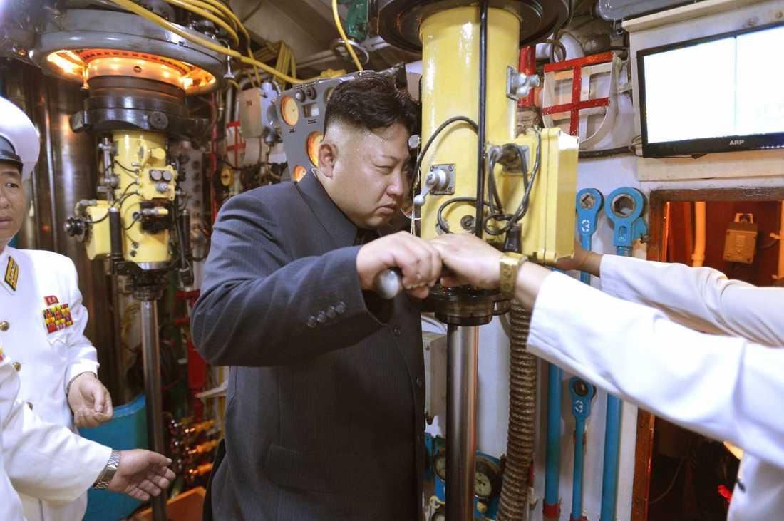 Kim Jong-Un tittar på horisonten genom ett periskop.