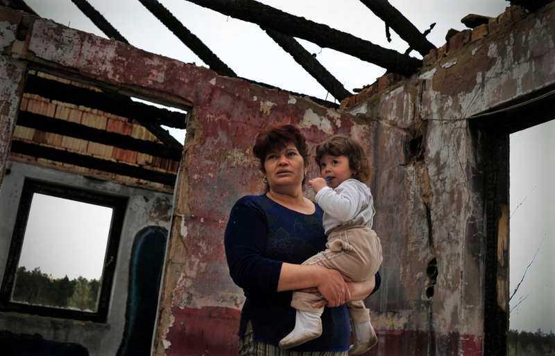 utsattErzsebet Csorbas son och sonson mördades när gardet kom till Tatárszentgyörgy. Här står hon med barnbarnet Erzsi i familjens hus som brändes ned. Foto