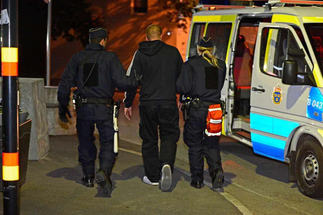En av de gripna männen vid Telefonplan förs in i polisbussen.