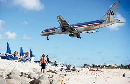 När man badar på stranden Maho Bay i Philipsburg gäller det att huka sig – här snuddar charterplanen vid palmtopparna på inflygningen till öns enda flygplats.