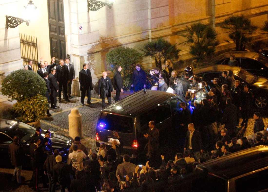 Berlusconi vinkar till sina anhängare när han lämnar sitt residens under lördagskvällen.