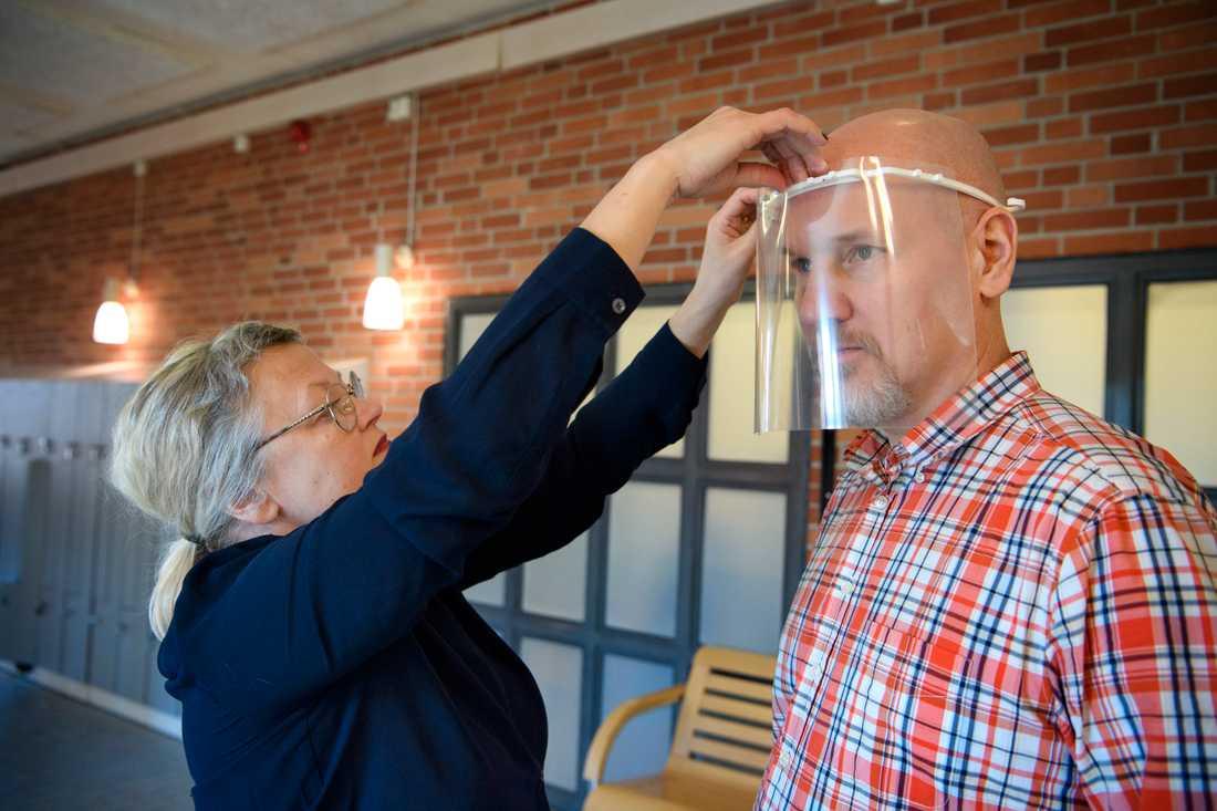 Rektor Monica Nyberg provar ett skyddsvisir på teknikläraren Robert Hegestedt.