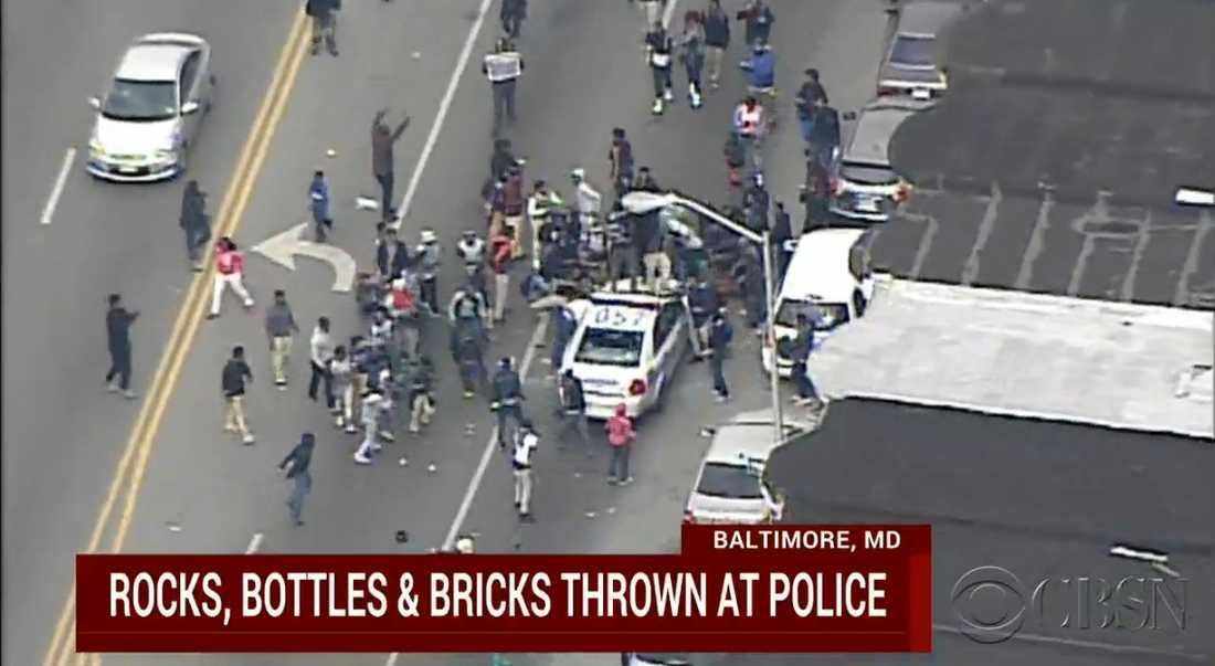 Människor samlades kring en polisbil och slog och hoppade sönder fordonet.