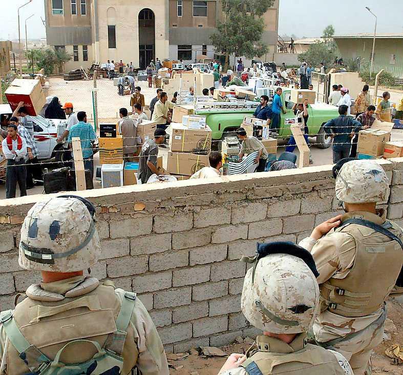 Amerikanska soldater tittar på medan en myndighetsbyggnad plundras i Bagdad.