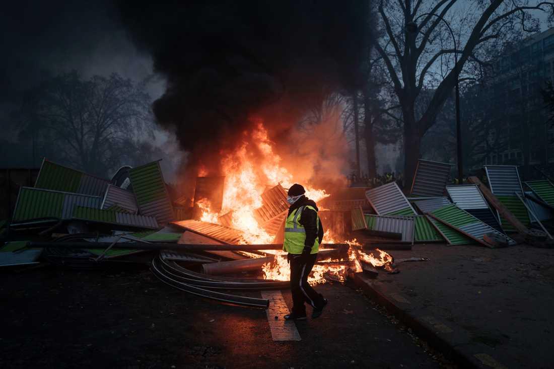 En demonstrant vid Triumfbågen på Champs-Elysees. Nu stoppas flera av helgens franska ligamatcher på grund av oroligheterna. Arkivbild.