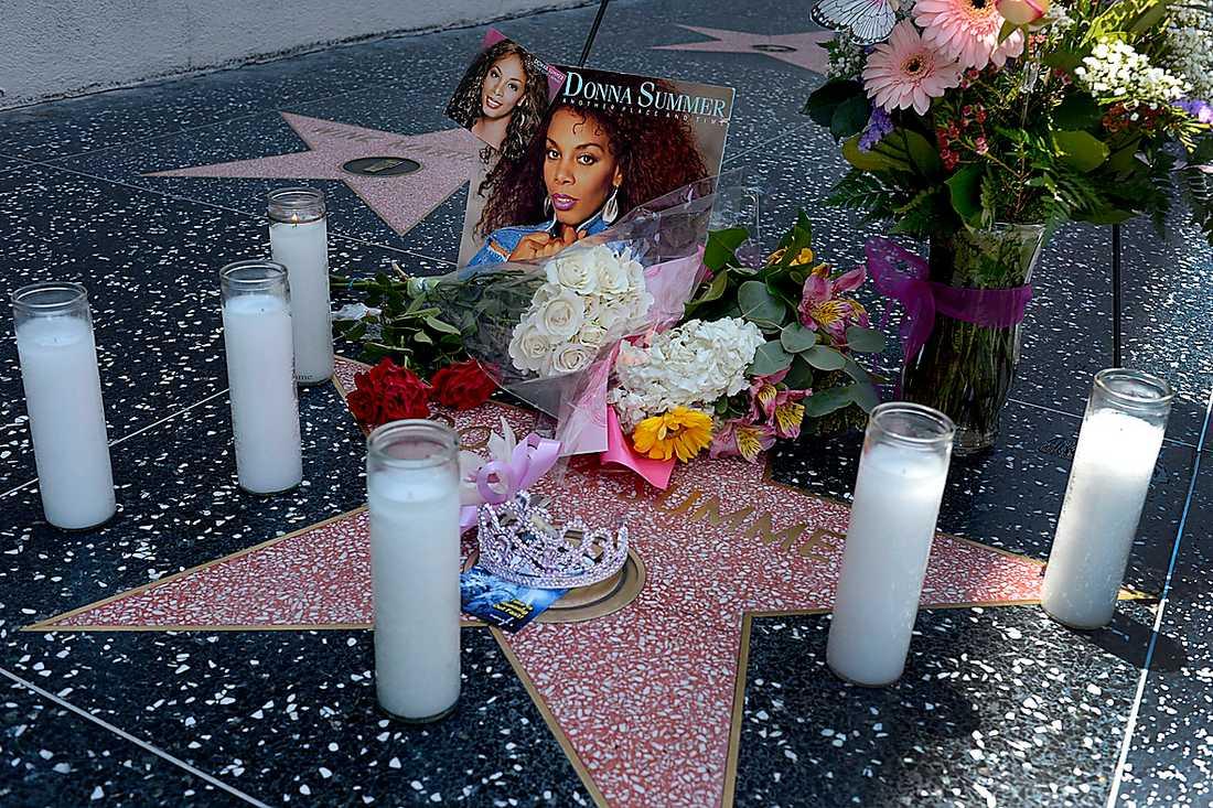 Sörjande fans lämnade blommor och ljus på diskodrottningens stjärna i Hollywood.