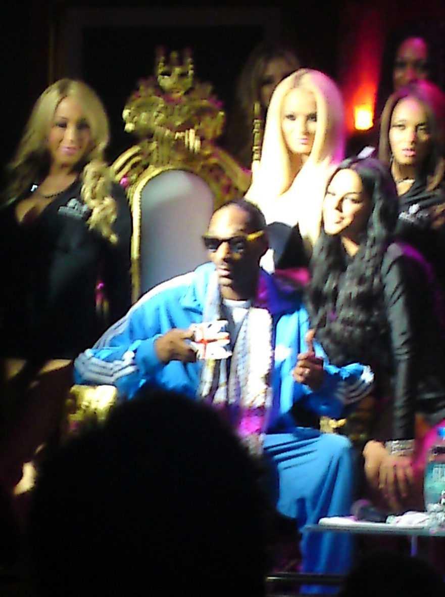 Snoop Dogg sitter på en guldtron, omgiven av 12 lättklädda unga kvinnor.