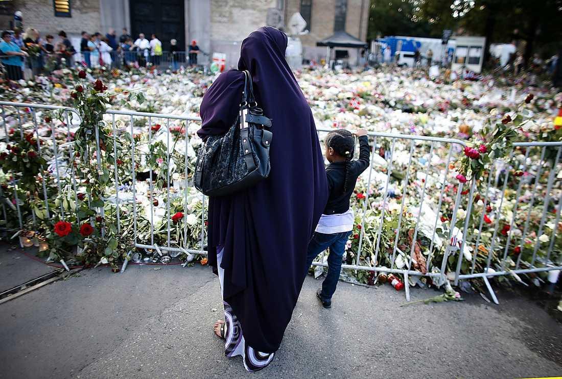 MINDES Vid ett hav av blommor utanför Oslokatedralen stannade en muslimsk kvinna och hennes barn till i går. Flaggor vajade på halv stång en vecka efter terrordådet.