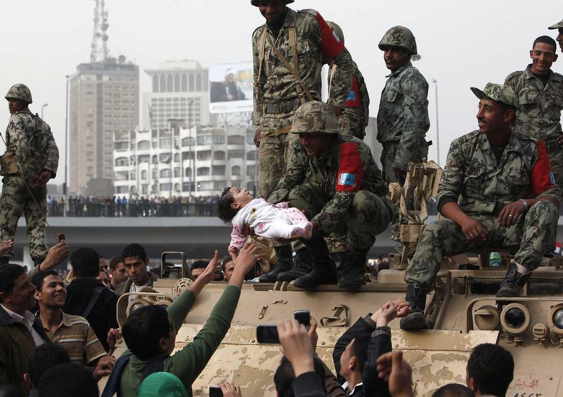 i centrum Tusentals männikor samlades på Kairos gator i går. Här lyfter en egyptisk soldat på ett stridsfordon försiktigt upp en liten ettårig flicka samtidigt som flera demonstranter tar bilder. Foto: ASMAA WAGUIH/REUTERS