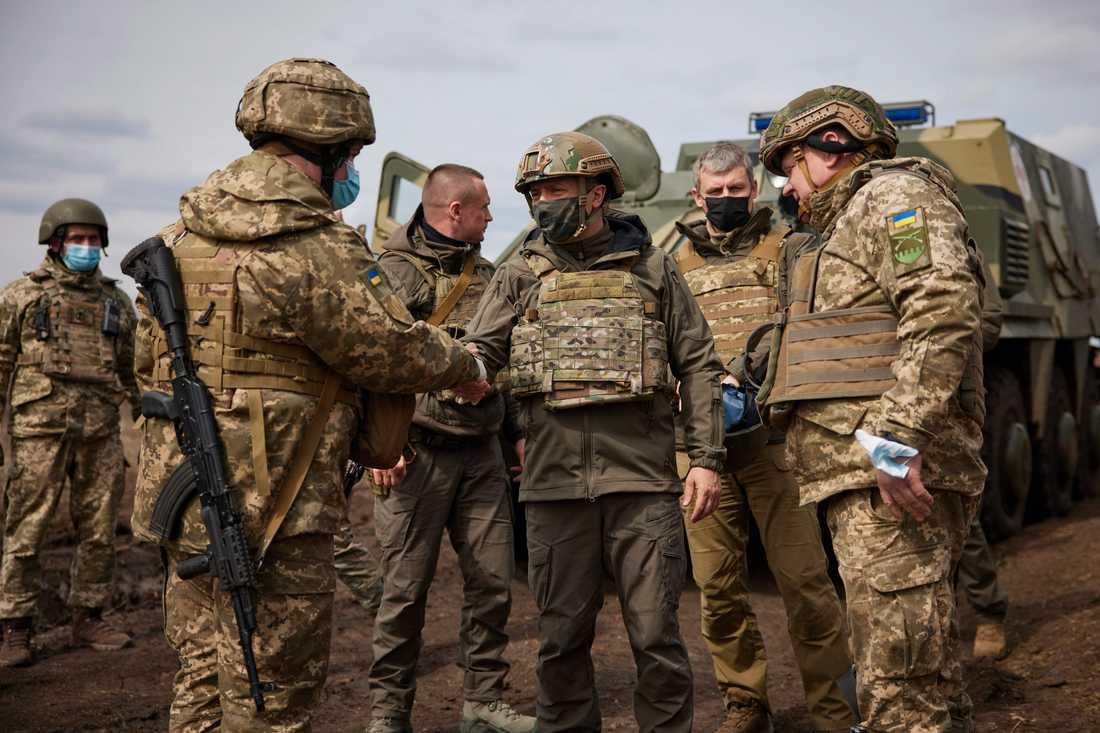 Ukrainas president Volodymyr Zelenskyj (trea från höger) skakar hand med en ukrainsk soldat i konfliktområdet i östra Ukraina. Arkivbild.
