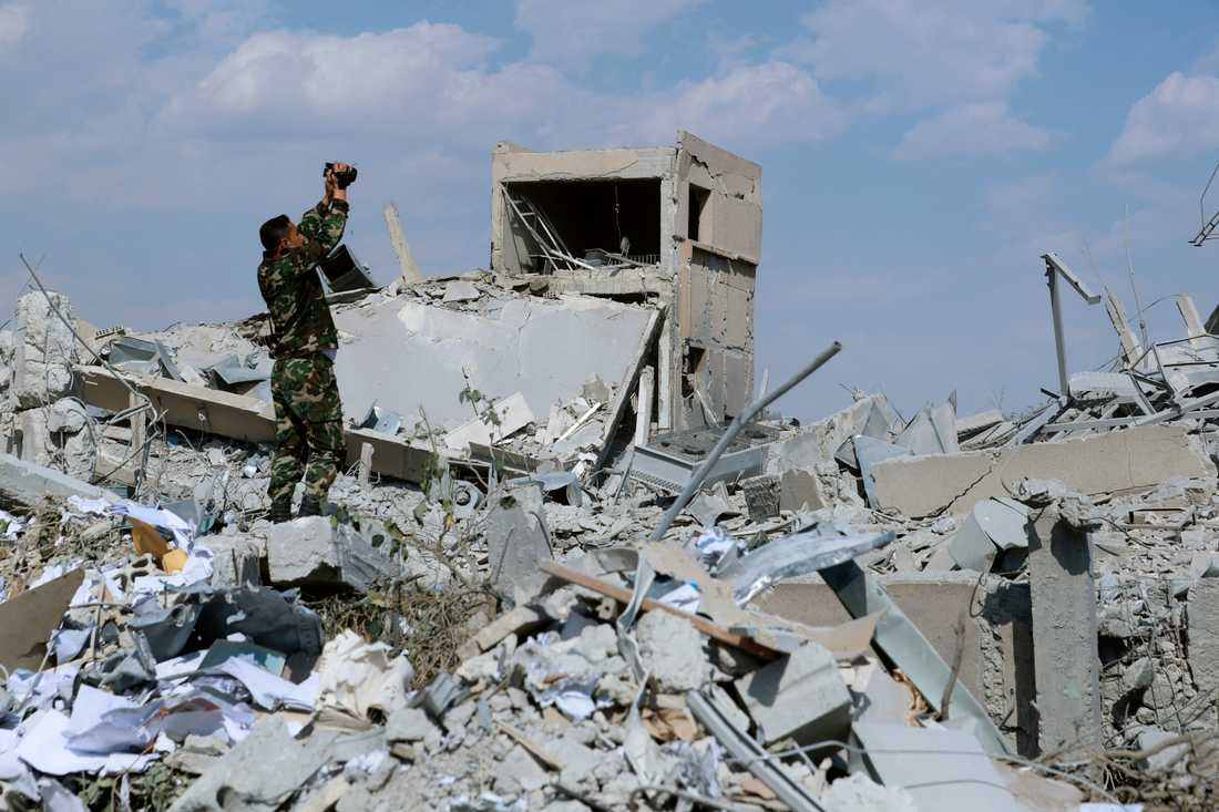 En syrisk soldat filmar förödelsen efter det USA-ledda flyganfallet i april mot en syrisk forskningsanläggning. Arkivbild.