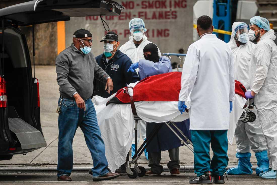 Sjukvårdspersonal hjälper till att transportera bort en person som dött av coronaviruset i New York.