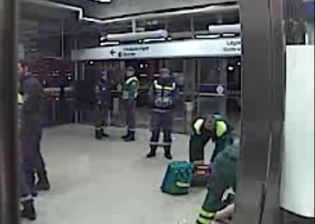 Här kämpar rånoffret för sitt liv och får hjälp av ambulanspersonal, vakter och polis.