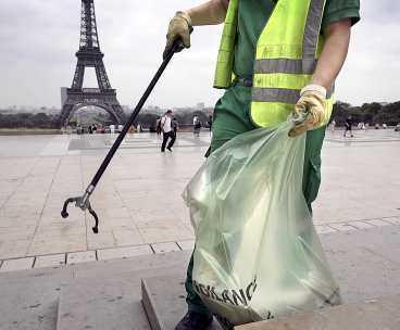ren taktik En av Paris många renhållningsarbetare plockar skräp rent runt Eiffeltornet. Stadens satsning på renhållning är en del av taktiken för att ta hem OS 2012.
