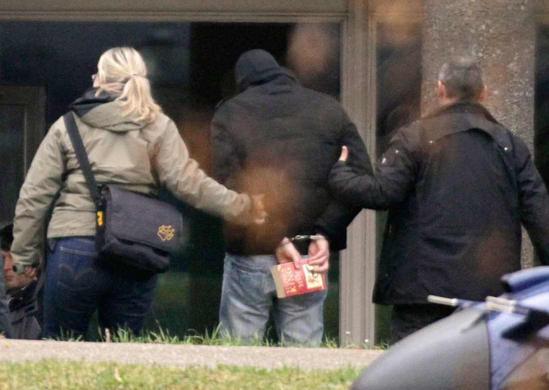 En misstänkt medhjälpare till den nazistiska mordligan förs bort av polis. I sin hand håller han en bok av skräckmästaren Stephen King.