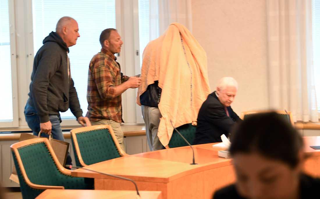 Den tidigare Tre Kronor-spelade var täckt av en filt när han fördes in till häktingsförhandlingen.