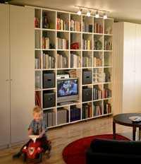 Multiförvaring i vardagsrummet. Här har standard-garderober kombinerats med en hylla i mdf-board som snickrats på plats.