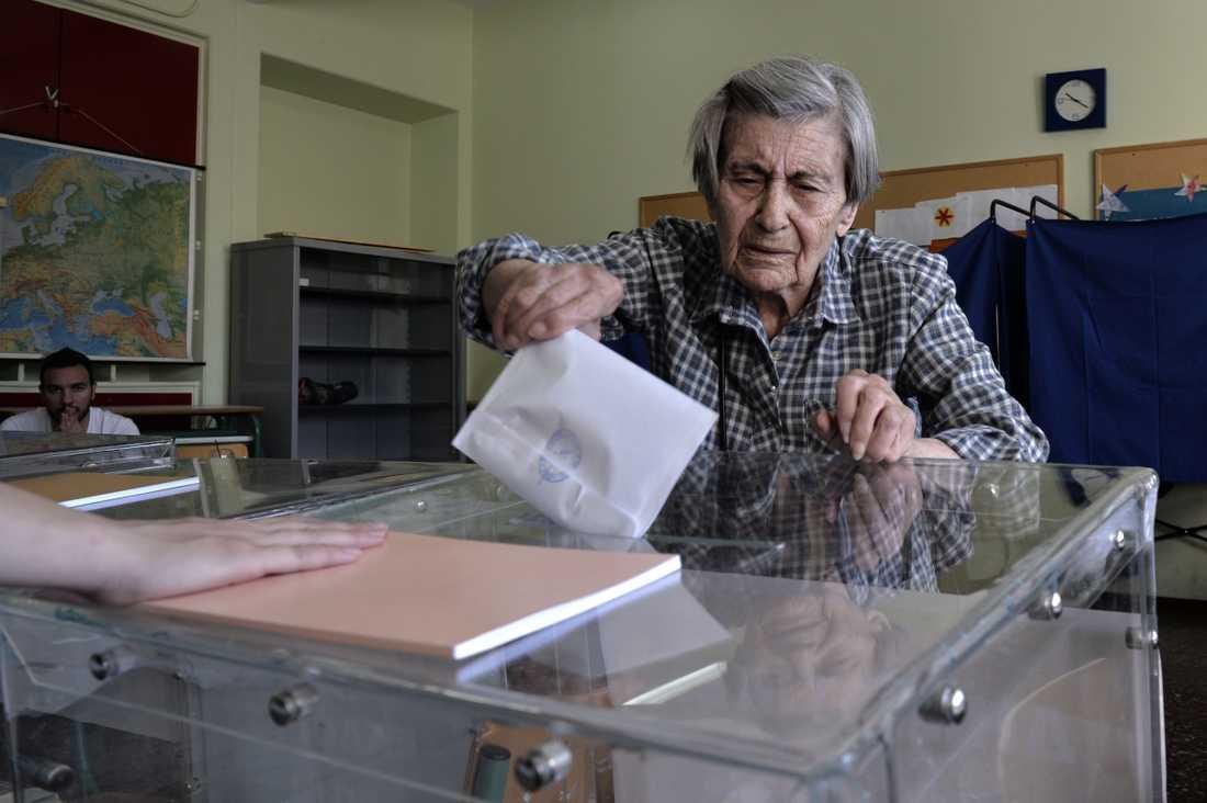 En kvinna avlägger sin röst i en vallokal i Aten.