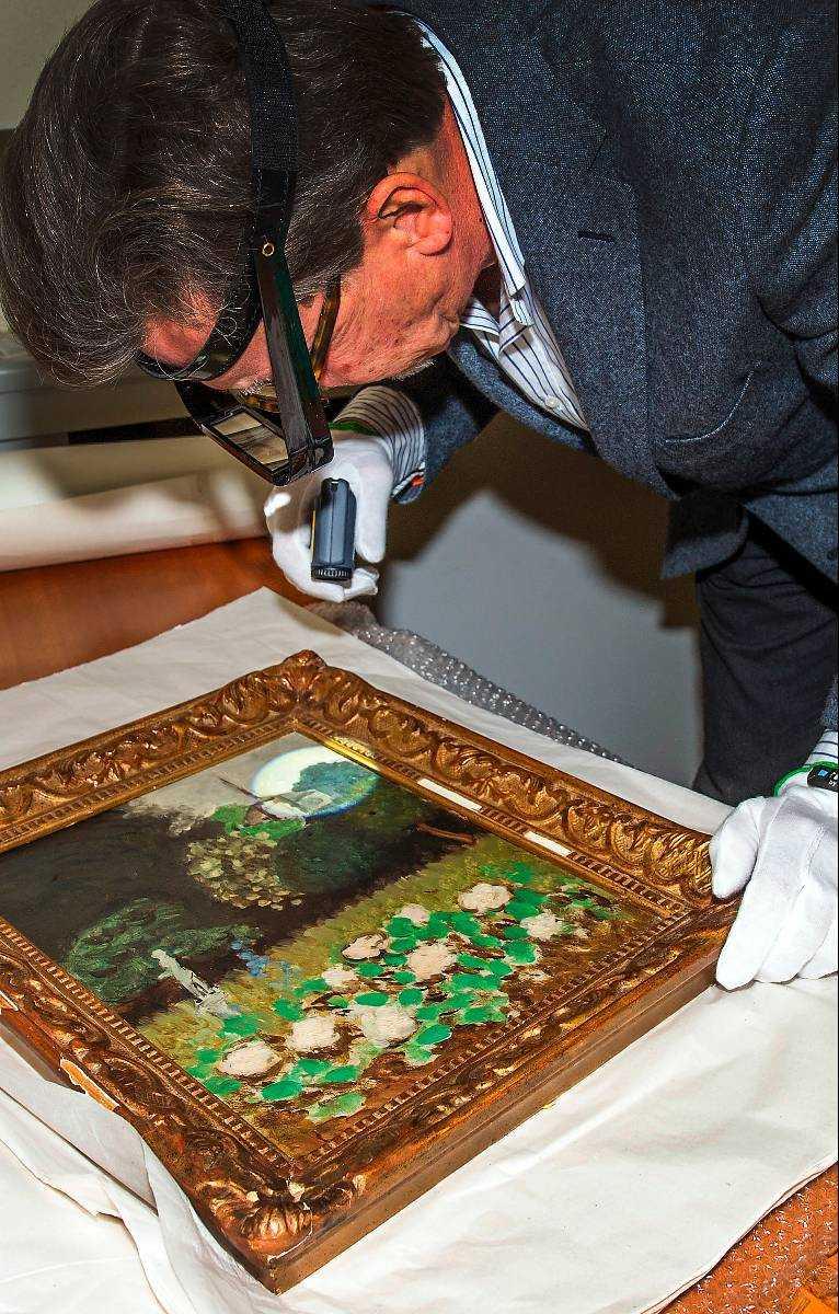 """Lars Byström undersöker """"Le Jardin"""" för att försäkra sig om att det är originalet."""