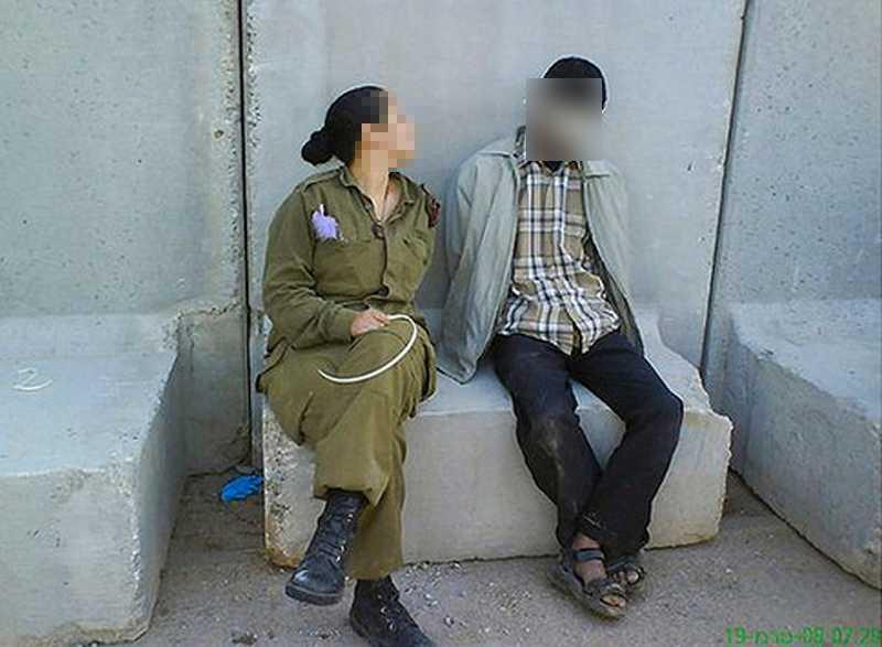 Den israeliska ex-soldaten lutar sig in mot den palestinske fången, som bär ögonbindel. Kvinnan la sedan ut bilderna Facebook.