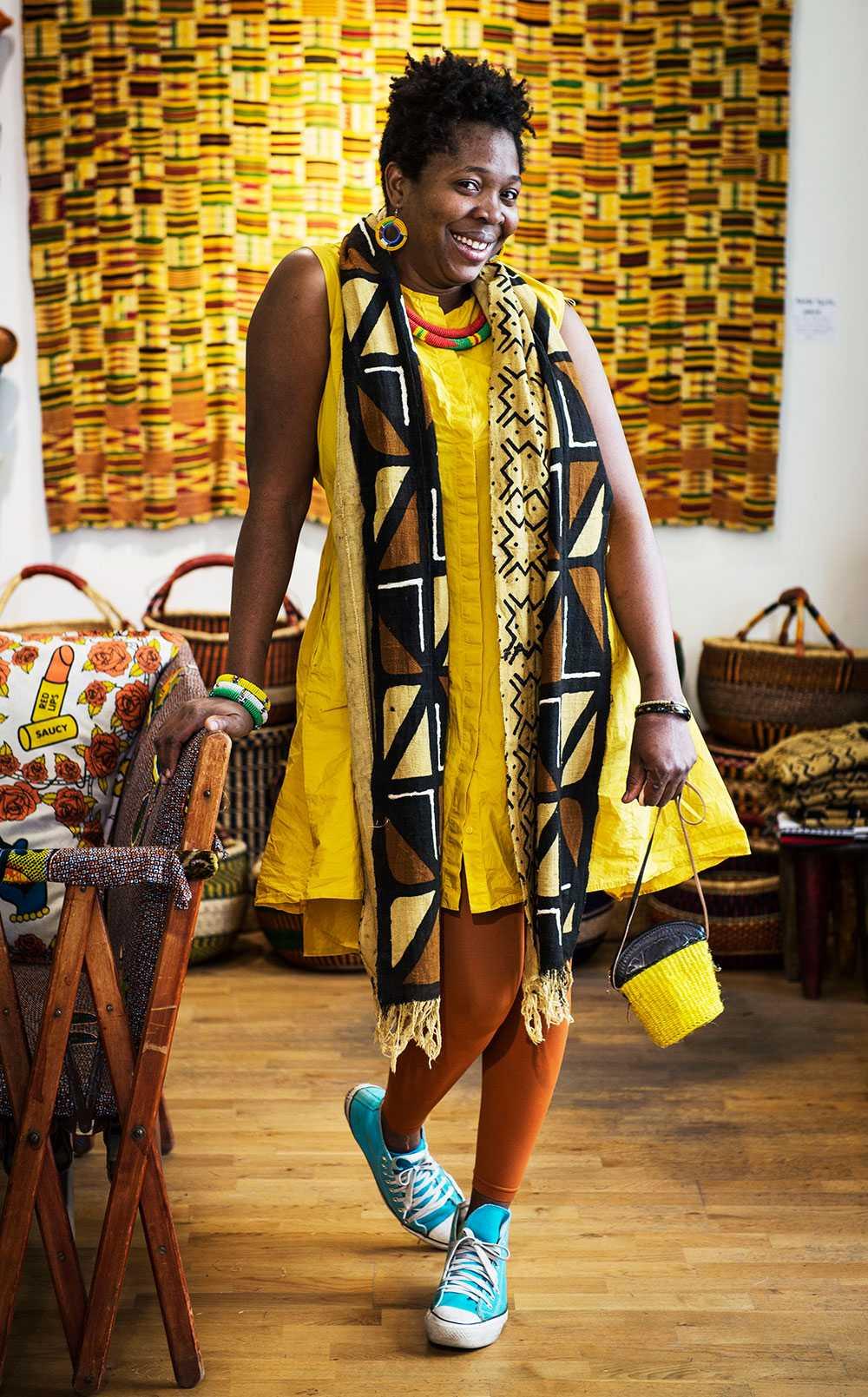 """FÄRGÄLSKARE  Funmi Peters från Nigeria driver sedan tre år tillbaka butiken Colours of Africa i Stockholm. """"Där jag kommer ifrån, betyder färger väldigt mycket. Folk vill ha uppmärksamhet och klär sig i mönstrade färgglada kläder. Du ser nästan aldrig någon gå klädd i svart, förutom när de har sorg"""", säger hon."""