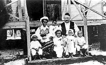 GIFTE SIG MED HÖVDINGENS DOTTER Carl E Petterson med sin fru, kannibalhövdingens dotter Sindu, utanför hemmet på ön Simberi i Söderhavet klädda i Österåkerdräkter. Barnen (från vänster): Calle, lille Erik i mammas knä, Hasse står mellan mamma och pappa, Elsa, Anna och Villy. Familjen Petterson fick ytterligare tre barn: John, Max och Sindu.