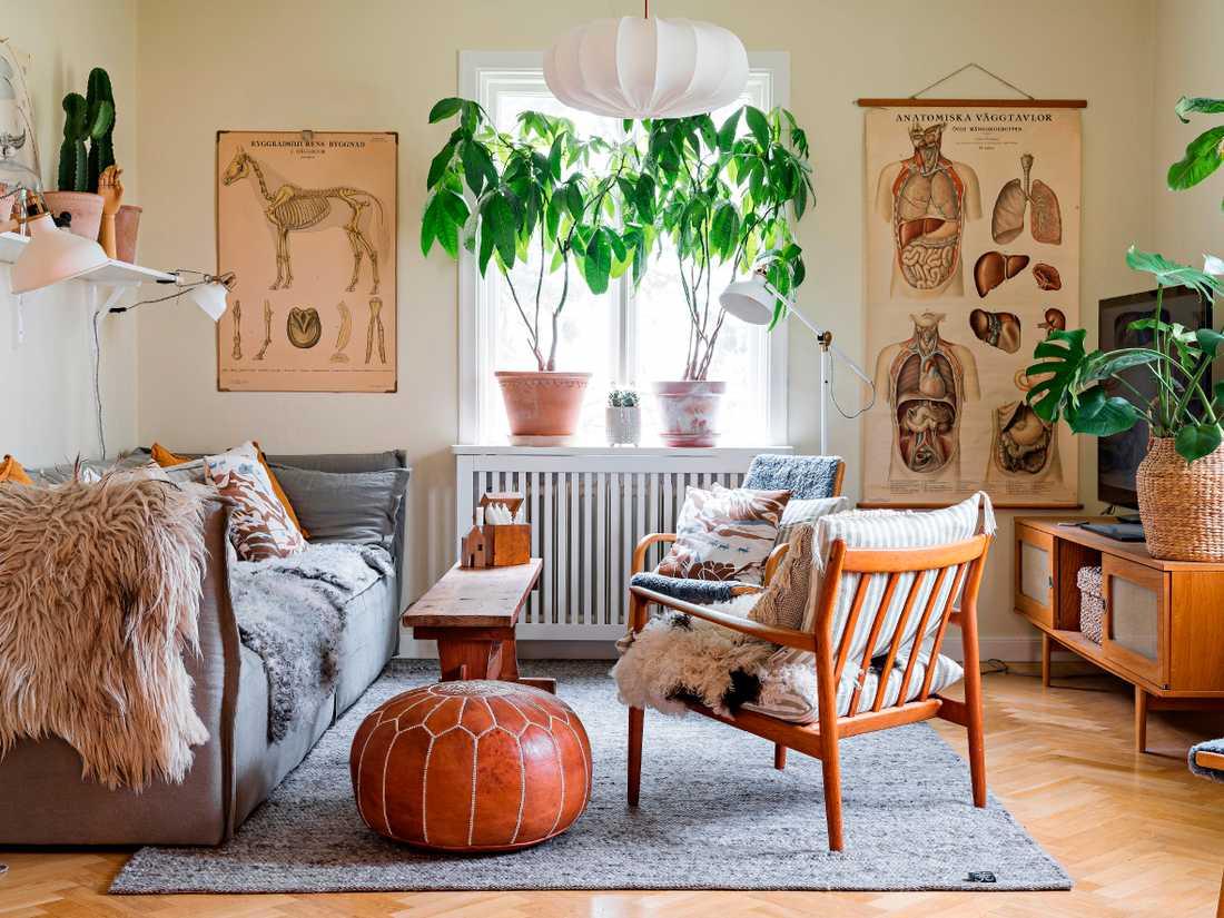 Vardagsrummet går i milda grå och beige toner. Fåtöljen är en dansk stol designad  av Grete Jalk och som Frida hittade på den lokala återvinningsstationen för några år sedan. Soffan kommer  från Hemdesigners, puffen  från Marockodesign och  planscherna är loppisfynd.