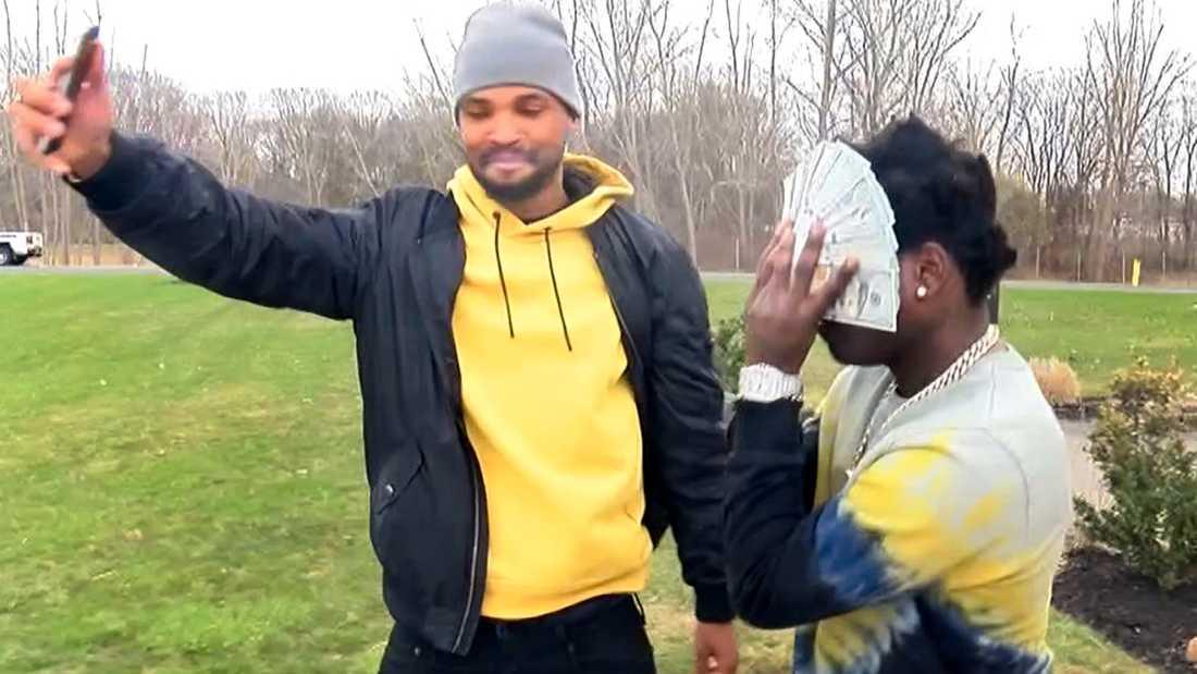 Bill Kapri, mera känd som rapparen Kodak Black, gömmer ansiktet bakom 100-dollarssedlar när han lämnar häktet mot borgen.