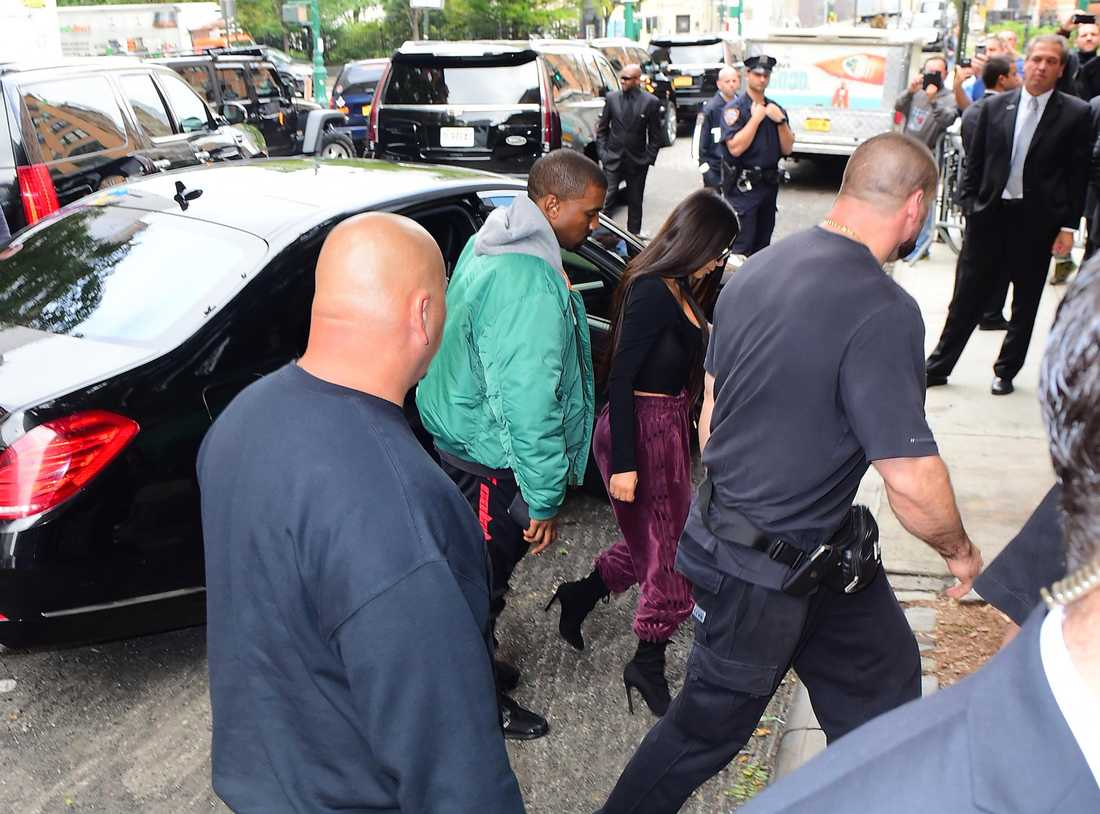 Kim Kardashian och Kanye West omgiven av säkerhetspersonal.