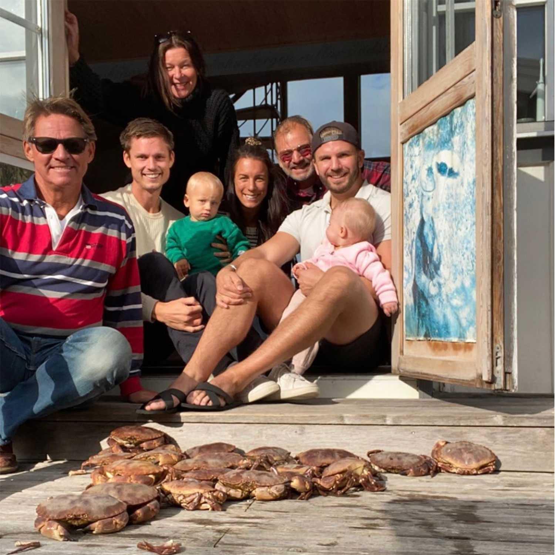 Lotta Engberg tillsammans med Mikael Sandström och hans son Marcus, dennes fru Sandra med lille Bernhard och Sandströms bror Jeppe och hans son Martin med lilla Livia i knät. Och några av de 22 fångade krabborna.
