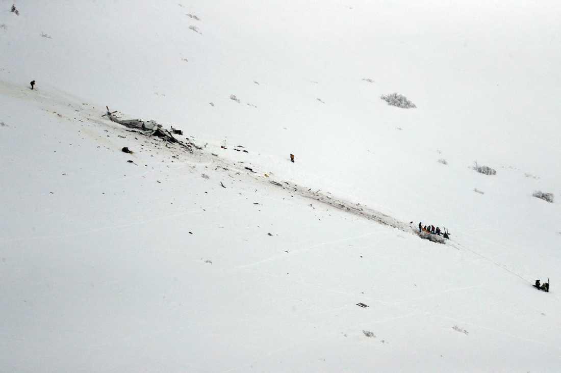 Räddningsarbetare kämpar sig upp mot den kraschade helikoptern.