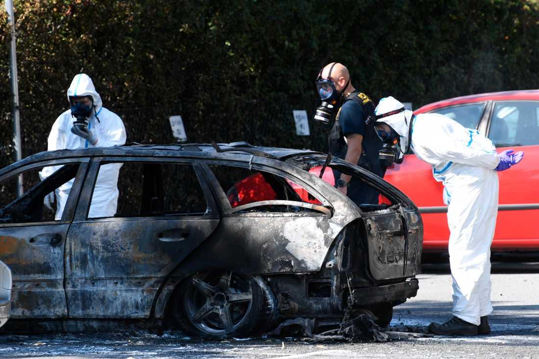 Polis och kriminaltekniker undersöker en utbrunnen bil på Stadiongatan efter skjutningen i Malmö.