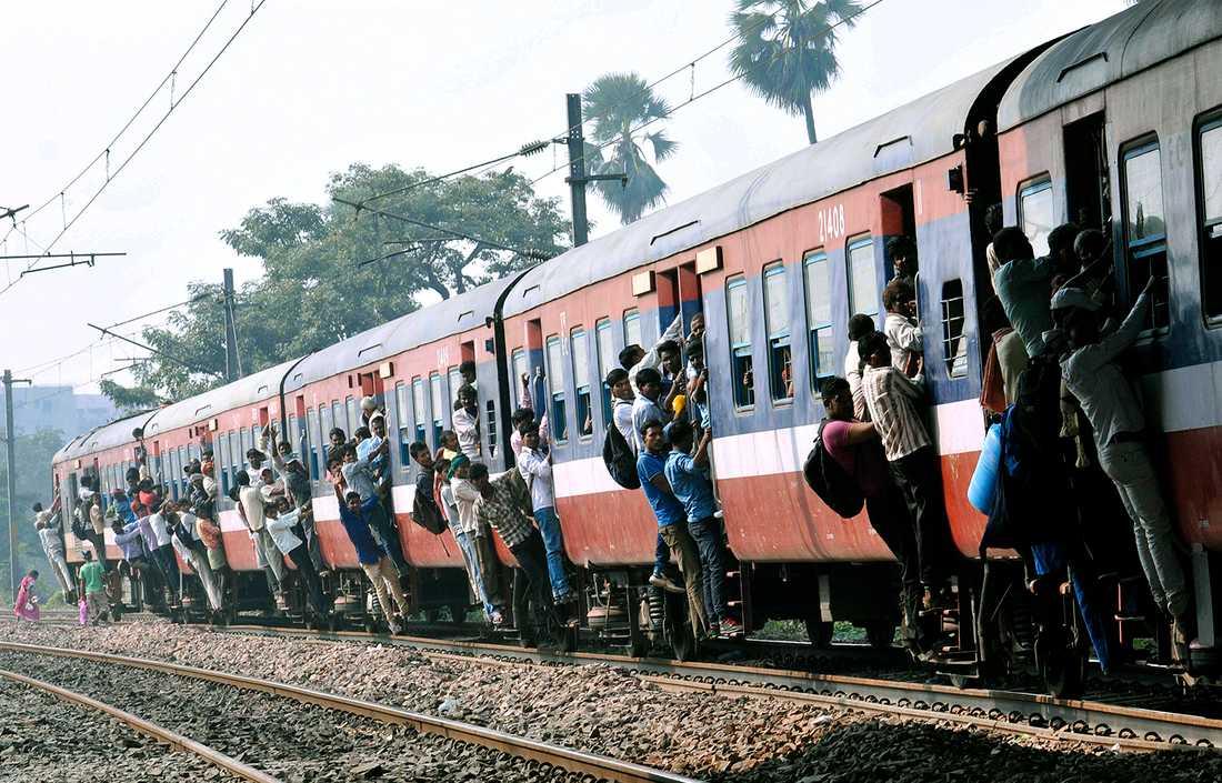 HEM TILL HELGEN Tågresenärer hänger i dörrarna till ett trångt tåg vid Gulzarbagh järnvägsstationen i Patna, Bihar, Indien. Många vill komma hem till den hinduiska festivalen Chath Puja. Indien har en av världens största järnväg med fler än 18,5 miljoner passagerare per dag.