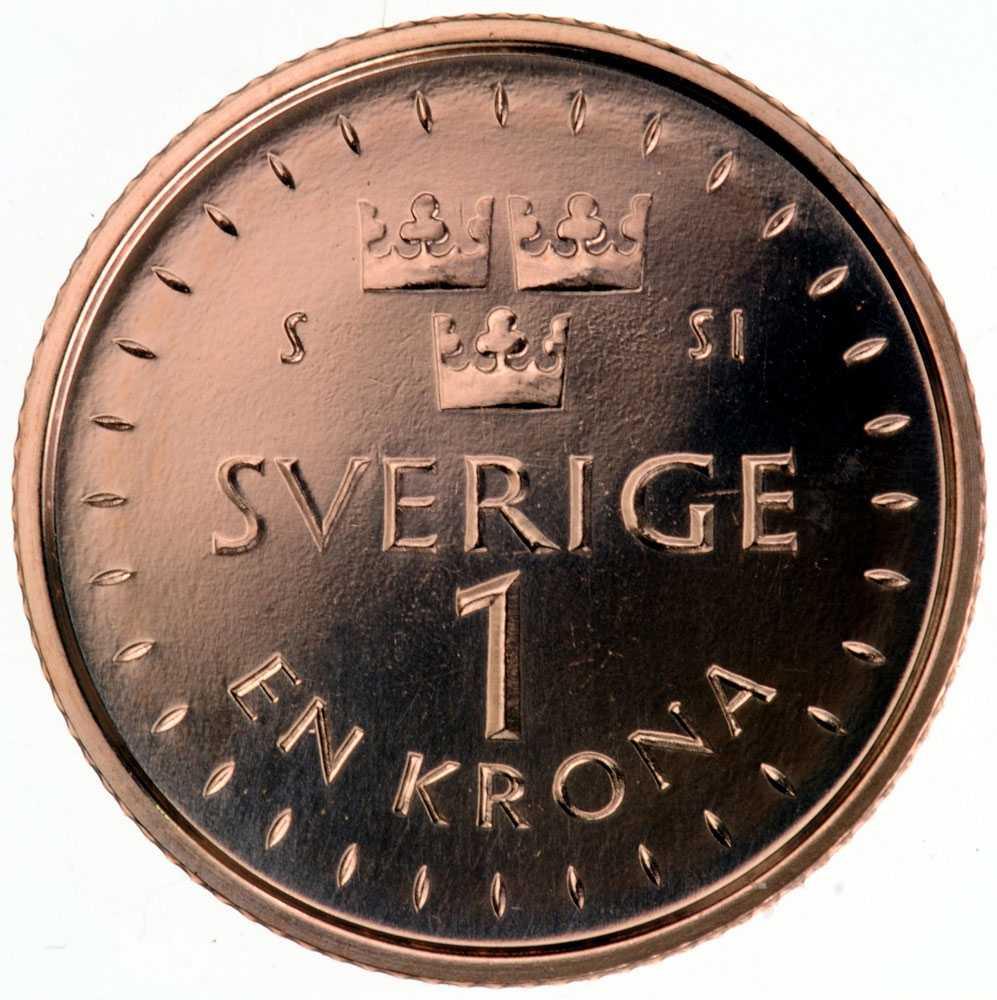 """Nya 1-kronans baksida. Strecken på mynten symboliserar solens strålar. Solen, i Ted Gärdestads """"Sol, vind och vatten""""."""