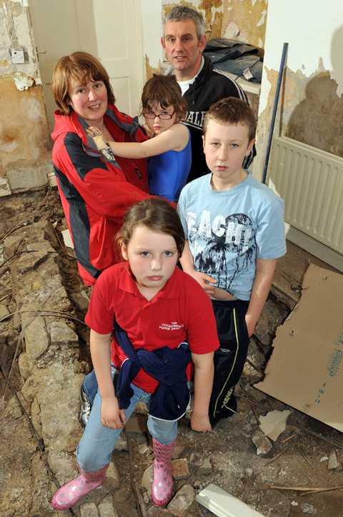 hem i spillror Familjen Bells hem ligger på Main Street i Cockermouth där vattnet steg omkring två meter. De drabbades hårt. Mamma Cathrine, pappa William, Gemma, 4, Kate, 8, och Robert, 11, står i ett av rummen på undervåningen som rivits ut för att torka ur grunden.