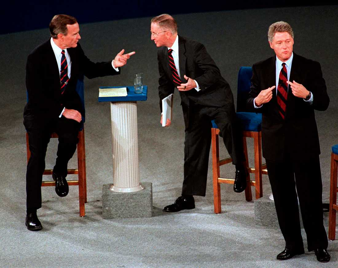 n this Oct. 15, 1992, file photo, President George H.W. Bush, left, talks with independent candidate Ross Perot as Democratic candidate Bill Clinton stands aside at the end of their second presidential debate in Richmond, Va.