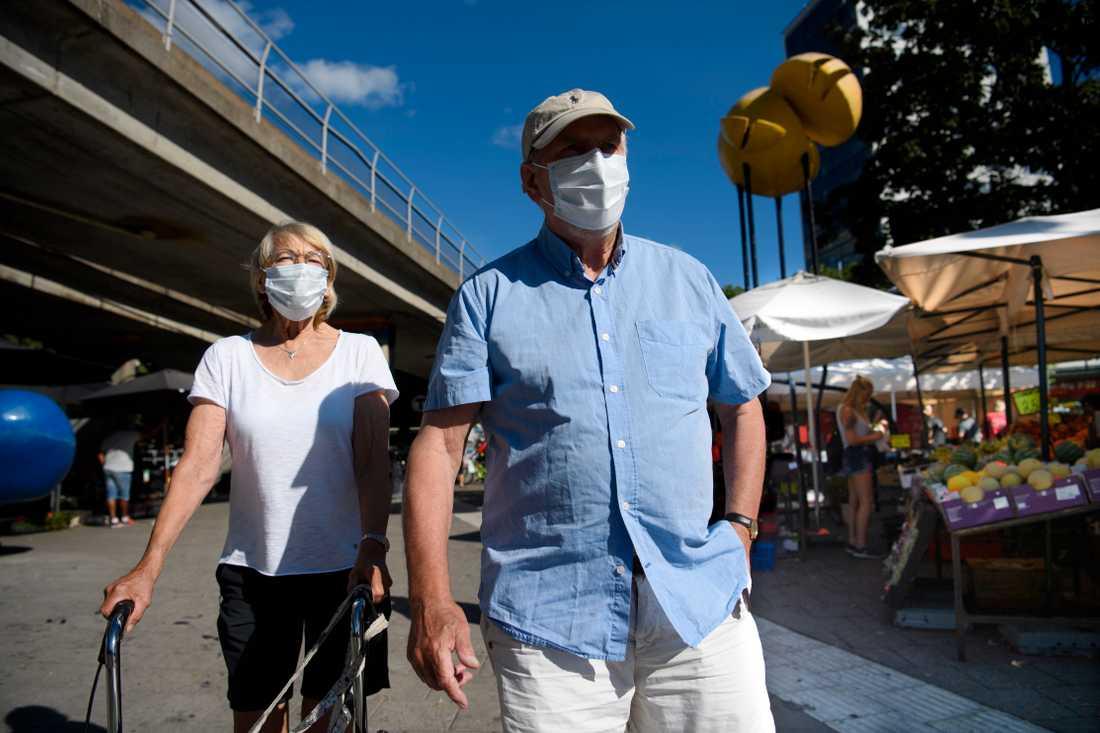 Äldre par med munskydd som är ute och går.