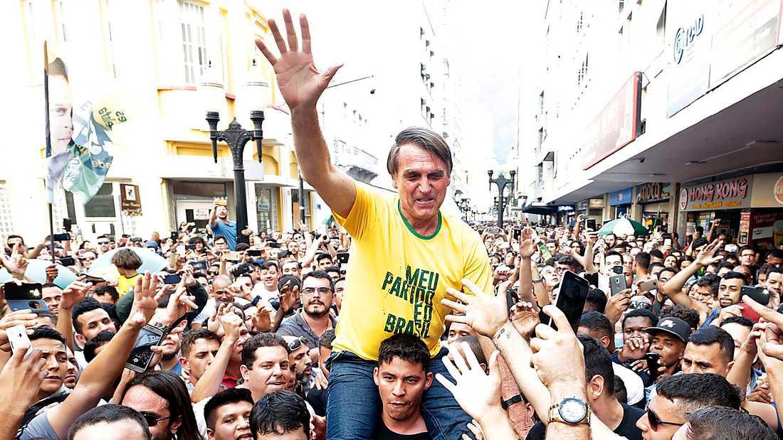 SEGERSÄKER Den högerextreme presidentkandidaten Jair Bolsonaro bärs fram av supportrar under presidentvalskampanjen. Strax efter att bilden togs knivhöggs han – en attack som stärkte hans position ytterligare.