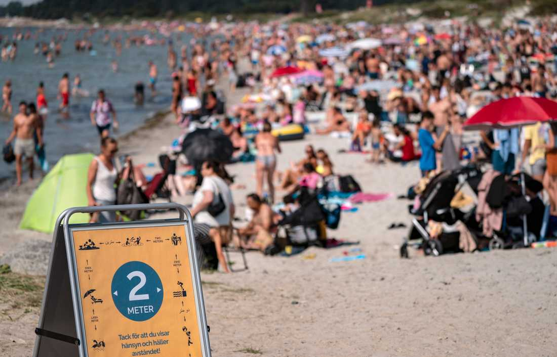 En skylt påminner om att hålla avstånd på stranden i Lomma, Skåne. Polisen i Sverige har fått in många samtal om trängsel på badstränder.