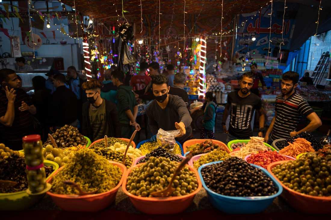 En försäljare av inlagda grönsaker bär munskydd på marknaden Zawiya i Gaza City. Bilden är från den 28 april.