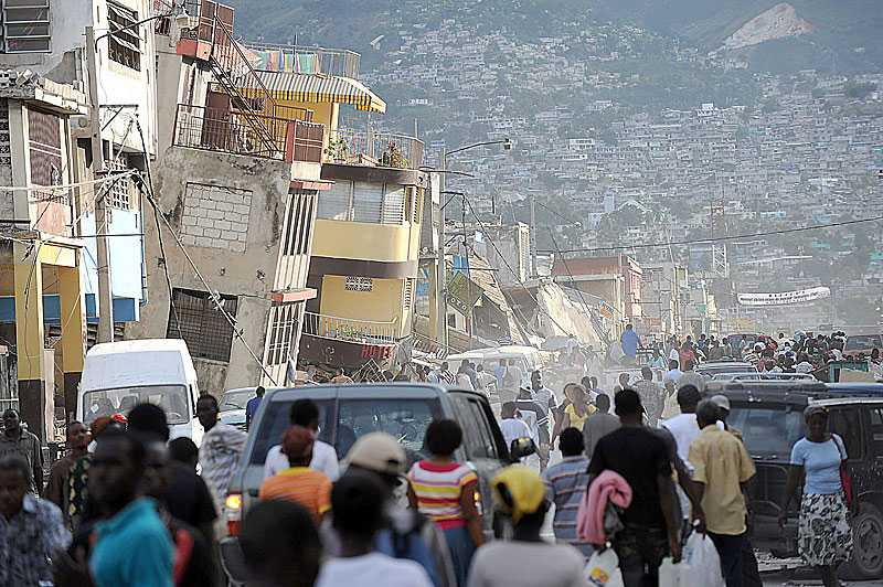 RASRISKEN STOR De hus som inte rasade direkt i jordbävningen är många gånger svårt skadade och riskerar att rasa. Invånarna samsas med några få bilar mitt i gatan för att undvika att skadas.